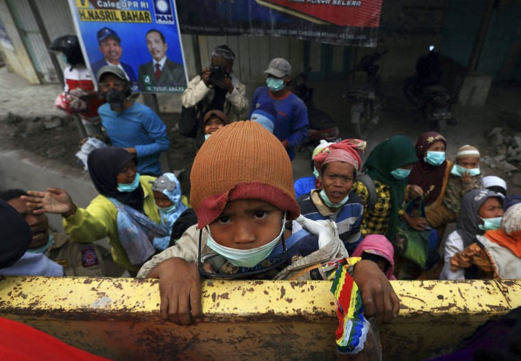 A child climbs onto a truck during an evacuation as ash from Mount Sinabung volcano hit Payung village in Karo district, Indonesia's North Sumatra province, January 8, 2014. (REUTERS/Beawiharta)