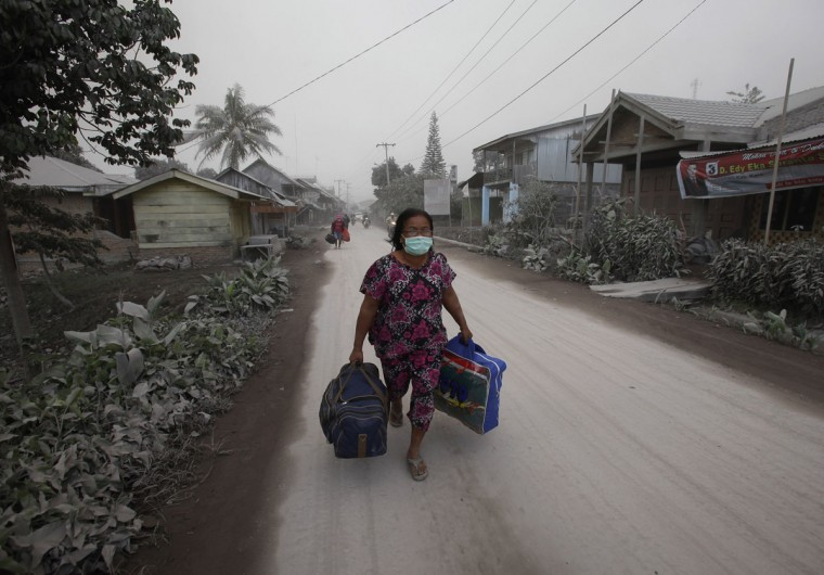 A villager carries her belongings during an evacuation after ash from Mount Sinabung volcano hit Payung village in Karo district, Indonesia's North Sumatra province, January 8, 2014. (REUTERS/YT Haryono)