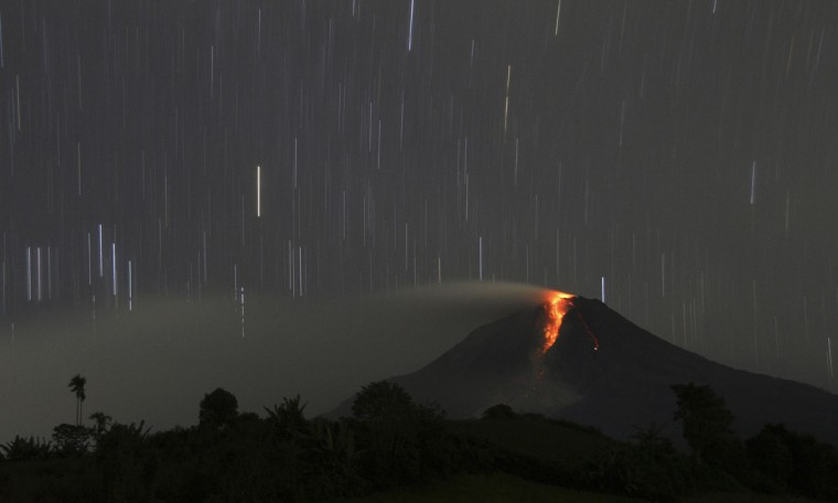 A long exposure photo shows star trails as Mount Sinabung volcano spews hot lava as seen from Jraya village in Karo district, Indonesia's North Sumatra province, January 9, 2014. (REUTERS/Roni Bintang)