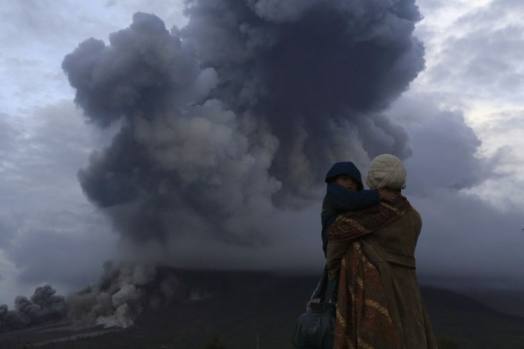 A mother holds her son as they watch the eruption of Mount Sinabung at Berastepu village in Karo district, Indonesia's North Sumatra province, January 10, 2014. More than 22,000 villagers have been evacuated since authorities raised the alert status for Sinabung to the highest level in November 2013. (REUTERS/Beawiharta)