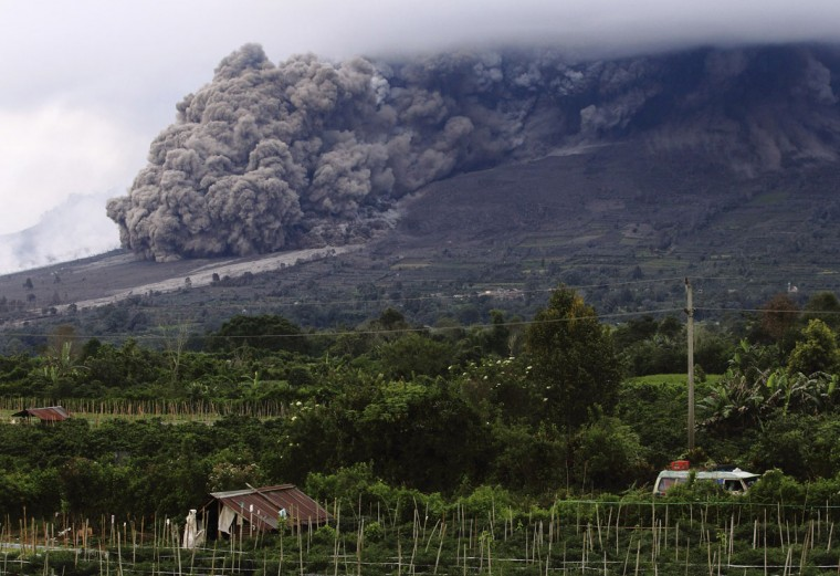 The Mount Sinabung volcano spews ash during an eruption, as seen from Berastepu village in Karo district, Indonesia's North Sumatra province, January 10, 2014. More than 22,000 villagers have been evacuated since authorities raised the alert status for Sinabung to the highest level in November 2013. (REUTERS/Beawiharta)