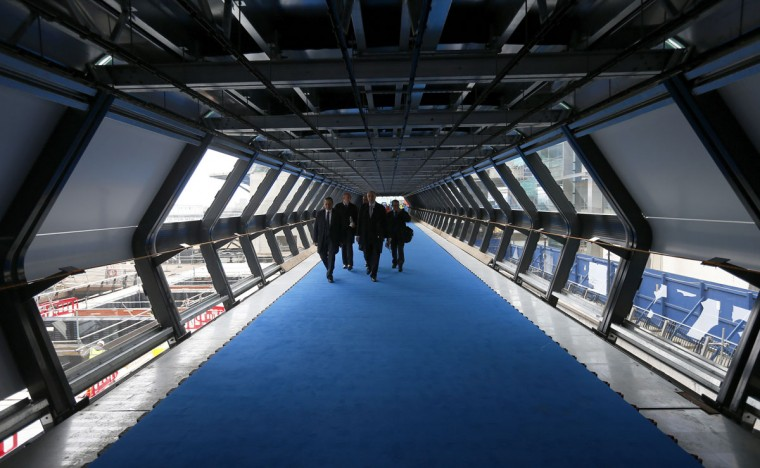 Workers walk down a station access corridor after attending the official announcement that a tunnelling machine had broken into the Crossrail station at Canary Wharf, in east London on May 31, 2013. (REUTERS/Andrew Winning)