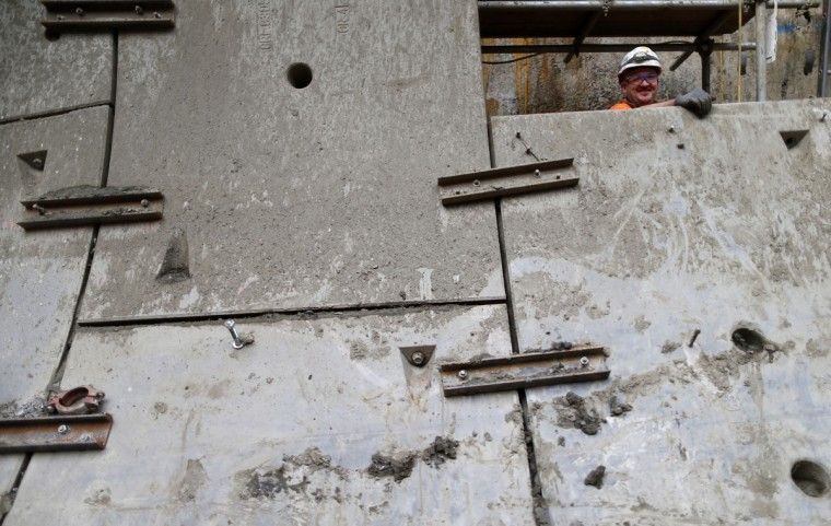 A worker stands behind concrete panels at the tunnel entrance at Crossrail's Stepney site in east London on September 25, 2013. (REUTERS/Andrew Winning)