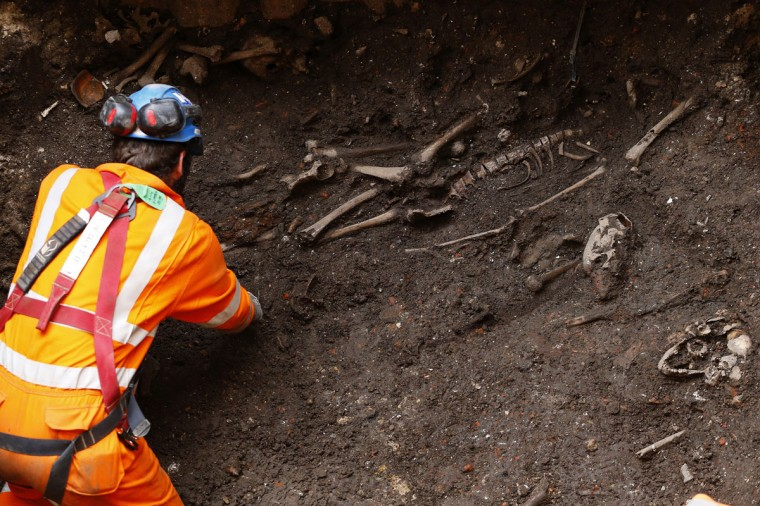 An archaeologist digs out skeletons from the site of the graveyard of the Bethlehem, or Bedlam, hospital next to Liverpool Street Station in the City of London on August 7, 2013. (REUTERS/Andrew Winning)