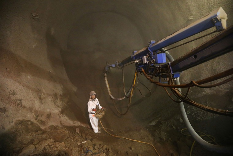 A technician sprays concrete to support caverns built to house the converging railway tunnels at Crossrail's Stepney site in east London on December 14, 2012. (REUTERS/Andrew Winning)