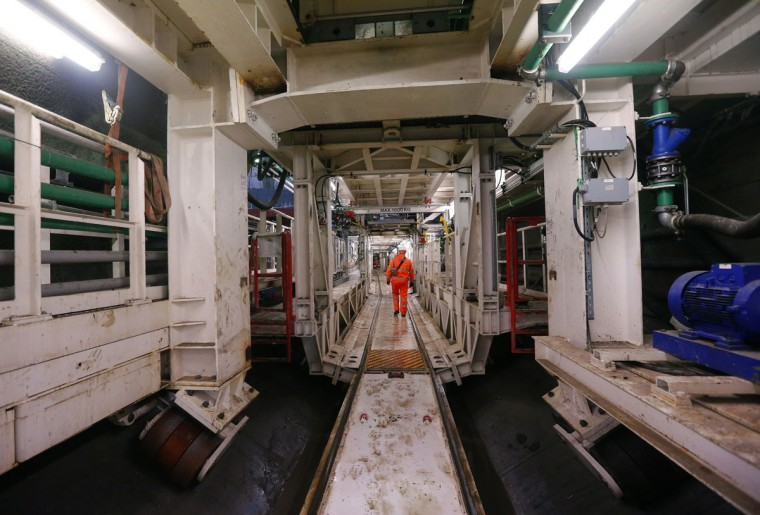 A worker walks inside a section of a tunnel-boring machine in one of the tunnels at Crossrail's Limmo Peninsula site in east London on December 14, 2012. (REUTERS/Andrew Winning)
