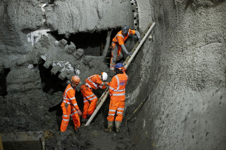 The crew of a tunnel-boring machine emerges after it broke through the wall at a major interchange on the Crossrail East to West underground railway link in Stepney, east London, on November 6, 2013. (REUTERS/Andrew Winning)