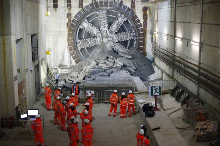 Workers look on after a tunnelling machine made the breakthrough into the station structure at Canary Wharf in east London on June 11, 2013. (REUTERS/Andrew Winning)