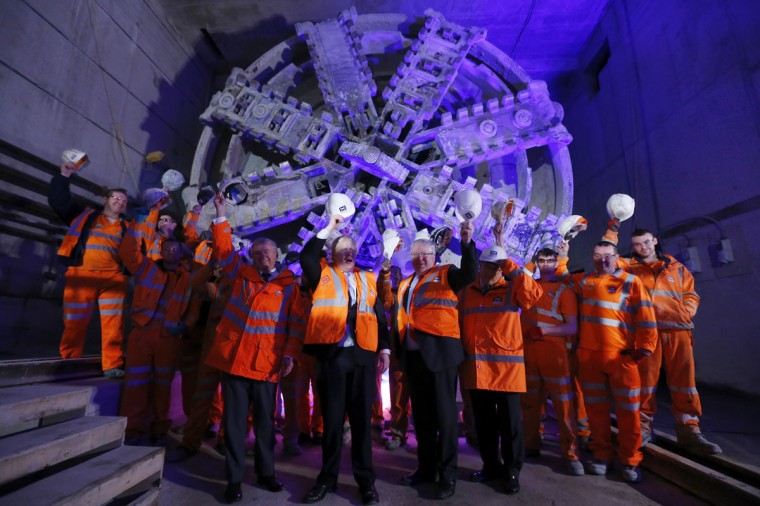 London Mayor Boris Johnson raises his hard hat as he poses with workers, the Secretary of State for Transport Patrick McLoughlin (right) and Andrew Wolstenholme, the CEO of Crossrail, at the official announcement that tunnelling machine Elizabeth has broken into the Crossrail station at Canary Wharf in east London on May 31, 2013. (REUTERS/Andrew Winning)