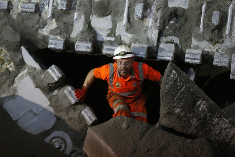 A worker walks over shattered concrete after the tunnelling machine made the breakthrough into the station structure at Canary Wharf in east London on June 11, 2013. (REUTERS/Andrew Winning)