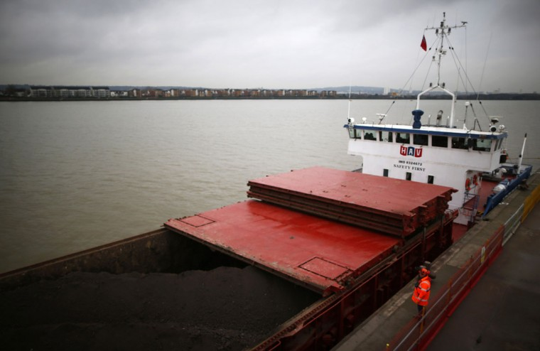 The chief officer of a bulk freighter oversees the loading of tons of earth generated by the construction of Crossrail onto his ship at a jetty on the Thames in east London on December 17, 2013. (REUTERS/Andrew Winning)