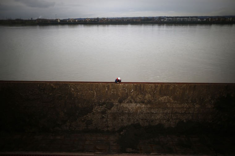 A member of the crew of a bulk freighter prepares his ship to receive tons of earth generated by the construction of Crossrail, at a jetty on the Thames in east London on December 17, 2013. (REUTERS/Andrew Winning)