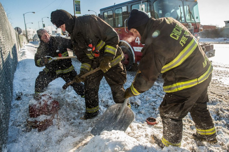 Firefighters from Engine 49 dig out a hydrant on Pershing Road in Chicago as the daytime temperature was registering minus 13 on Monday. (Zbigniew Bzdak/Chicago Tribune)