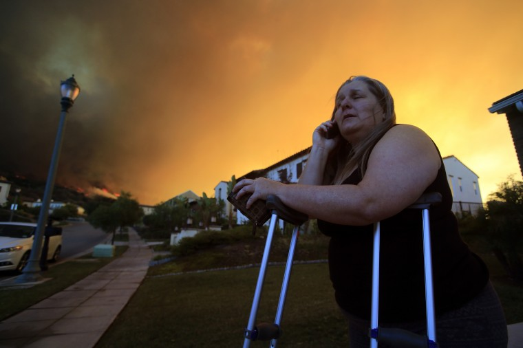 Glendora resident Cathy Doherty waits to be evacuated in the 500 block of Viewcrest Drive in Glendora as the Colby fire continues to burn Thursday morning, January 16, 2014, in the Angeles National Forest. The fire was reported at about 6 a.m. north of Glendora, a foothill community about 30 miles northeast of downtown Los Angeles. (Mark Boster / Los Angeles Times)