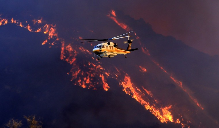 A water dropping helicopter flies by the Colby fire prior to a drop Thursday morning, January 16, 2014, in the Angeles National Forest. The fire was reported at about 6 a.m. north of Glendora, a foothill community about 30 miles northeast of downtown Los Angeles. (Mark Boster / Los Angeles Times)