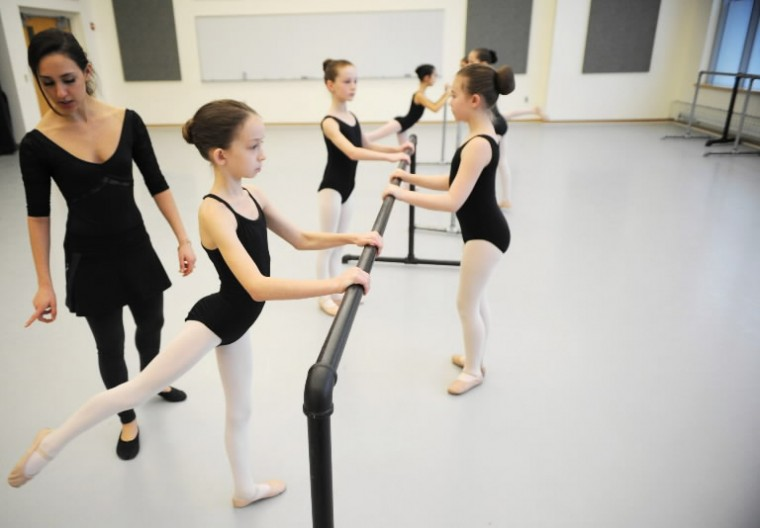 Dance instructor Analiese Umana watches for correct technique from Lidia Bridges, 10, of Towson as she porforms moves a the barre with fellow ballet students during a Towson University Community Dance ballet class at the Center for the Arts studio on Saturday, Jan 11. (Photo by Brian Krista/BSMG)