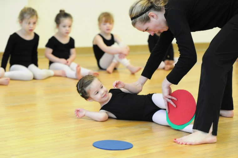 Candice Webster, director of education with Towson University Community Dance, works with three-year old student Lucy Decosimo of Radnor-Winston, as she rolls across the floor during a class at the Center for the Arts studio on Saturday, Jan 11. (Photo by Brian Krista/BSMG)