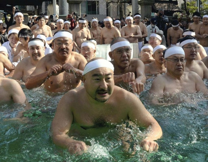 Dozens of people take a dip during the annual kanchu suiyoku midwinter cold water bath at Teppozu Inari Shrine in Chuo Ward, Tokyo, on Sunday. About 100 people prayed for good health and other wishes over the coming year while sitting for several minutes in a tub of 6 degrees C (about 42.8 degrees F) water set up at the shrine. Stand-alone photo. (The Yomiuri Shimbun)