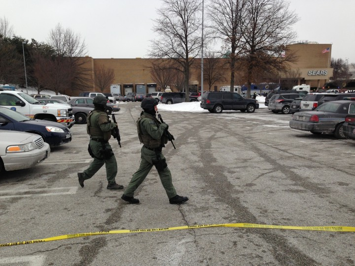 Police walk through the parking lot outside The Mall in Columbia in Columbia, Md., on January 25, 2014. A shooting incident inside the mall left at least three people dead, according to police. ( Washington Post photo by Peter Hermann)