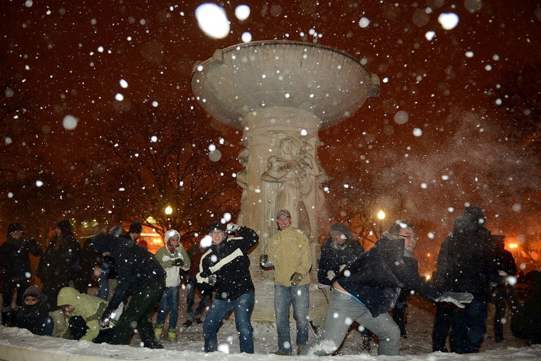 Tuesday's snowfall led to a snowball fight around the fountain at Dupont Circle in Washington. (for The Washington Post by Astrid Riecken)