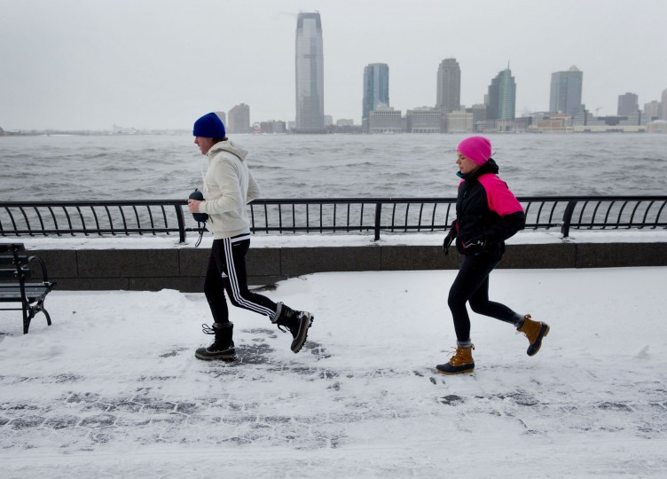 A couple jogs in the snow in the Battery Park City neighborhood of New York, U.S., on Friday, Jan. 3, 2014. Wind-driven snow whipped through New Yorkís streets and piled up in Boston as a fast-moving storm brought near-blizzard conditions to parts of the Northeast, closing roads, grounding flights and shutting schools. (Jin Lee/Bloomberg)