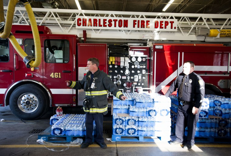 Police officers and firefighters hand out cases of water to those in need at the Charleston Fire Department Station One in Charleston, W.V., on Saturday, January 11, 2014. About 5000 gallons of a chemical used in the coal cleaning process leaked into the Elk River, forcing official to restrict water use by 300,000 West Virginia residents in nine counties. (Photo for The Washington Post by Ty Wright)