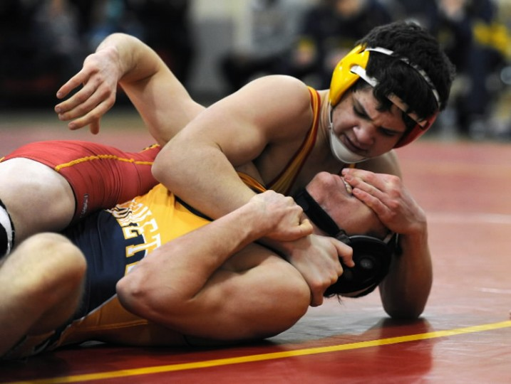 Calvert Hall's Noah Koski, top, gets a hand on the face of Catonsville's Luke Mercier as the two struggle for control on the mat during a wrestling match at Calvert Hall College in Towson on Tuesday, Jan. 28, 2014. (Photo by Jon Sham/BSMG)