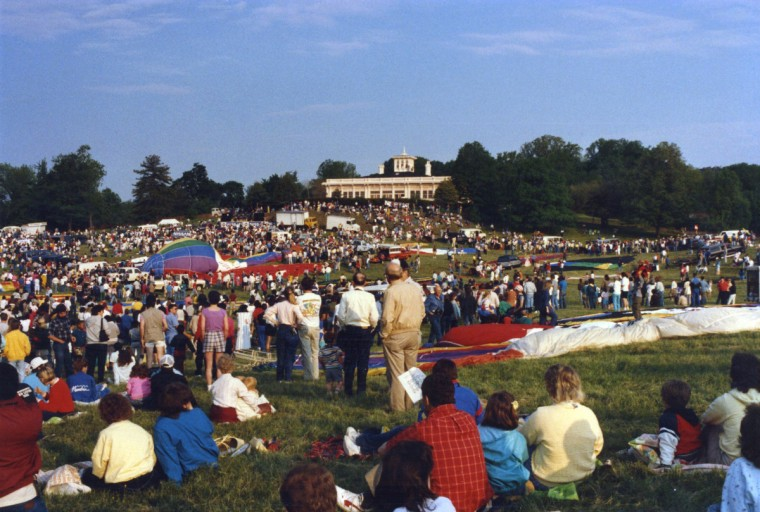 """Passing Fancies."" Hundreds once watched hot air balloons take riders up, up and away from the Grand Lawn at the Mansion House. The aerial extravaganzas were a passing Druid fancy. Today hundreds of children gather for Summer Camp Graduation Day. Others enjoy solitary walks and jogging, ethnic and social festivals, bands playing, family reunions, chestnut gathering, city farming, farmers market, tennis, swimming, football, basketball, softball, disc golf and golf practice shots. Many just sit at leisure. (Ernie Imhoff/For The Baltimore Sun)"