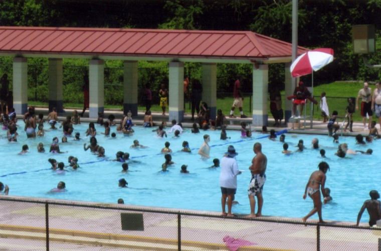 """Children of Summer."" Baltimore children learn tennis basics or swim near the East Road while older kids play disc golf near the old Reptile House or run and stroll around the lake and hills. The city is making park improvements. Until the 1950s, Jim Crow rules forced blacks and whites to use separate and unequal park tennis and swimming facilities. The Maryland Zoo's pet skunk Peppy delights marathoners, while a giraffe entrances two boys. The park is a refuge for peace and quiet as well as basketball, bicycling and socializing. Louis Rizzo returned home from World War II after serving on Liberty ships in battle-weary convoys. Now 92, he says Druid was ""The destination. Took girlfriends there for picnics. It was all very innocent. The park was peaceful, a good place for picnics and it was free."" It still is. (Ernie Imhoff/For The Baltimore Sun)"