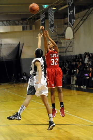Ryan Holder of Roland Park releases a three-point shot over the block attempt by Kaila Jennings of Seton Keough during a girls basketball game at Seton Keough High School on Friday, Jan 10.