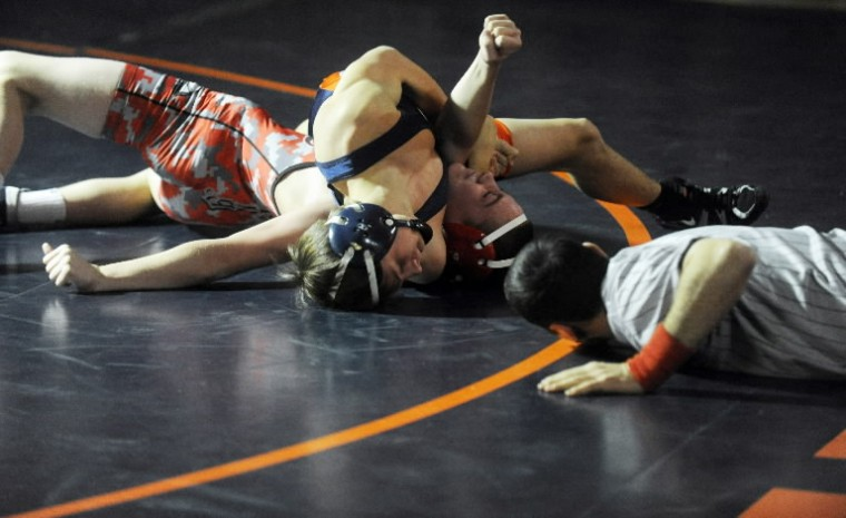 Trent Kilcarr of Reservoir, top, goes for a pin of Glenelg's Garrett Murray in the 120-pound weight class match during a wrestling meet at Reservoir High School on Thursday, Jan 9.