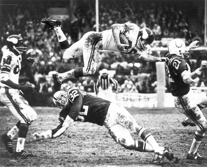 A Minnesota Viking player dives over Baltimore Colts Mike Curtis during game at Memorial Stadium on September 19, 1971. (Paul Hutchins/Baltimore Sun)