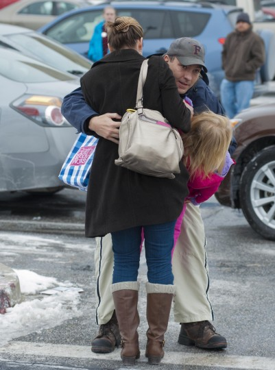 A father hugs his daughter and her mother during a shooting inside the Columbia Mall Saturday, Jan. 25, 2014. At least three people are confirmed dead, including the shooter, according to news reports claiming police as the source of the information. (Noah Scialom/Freelance)