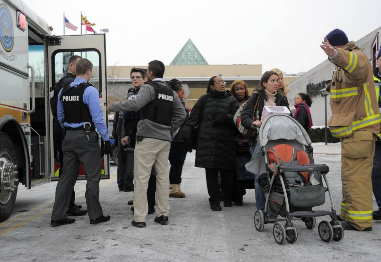 Rescue personnel help bystanders to evacuate the food court entrance during a shooting inside the Columbia Mall Saturday, Jan. 25, 2014. At least three people are confirmed dead, including the shooter, according to news reports claiming police as the source of the information. (Karl Merton Ferron/Baltimore Sun Staff)