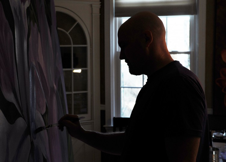Edward Williams, a Catonsville artist, is silhouetted by the window in his studio as he creates a large painting of flowers on canvas at his home on Thursday, Jan. 16, 2014. (Jon Sham/BSMG)