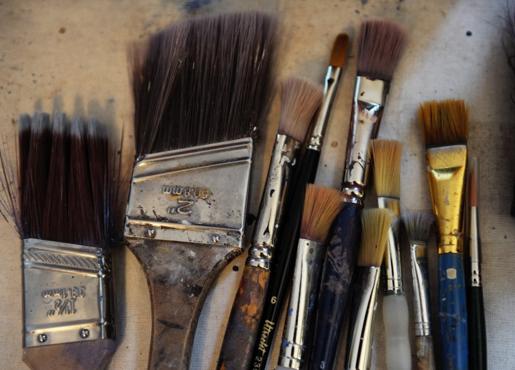 Several of Edward Williams' paint brushes are laid out on a table in his home studio in Catonsville as he works on a commissioned painting, Thursday, Jan. 16, 2014. (Jon Sham/BSMG)