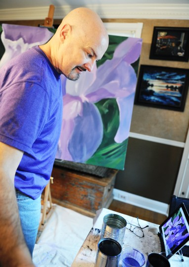 Edward Williams, a Catonsville artist, looks at his iPad displaying the painting of flowers he is working at his home on Thursday, Jan. 16, 2014. (Jon Sham/BSMG)