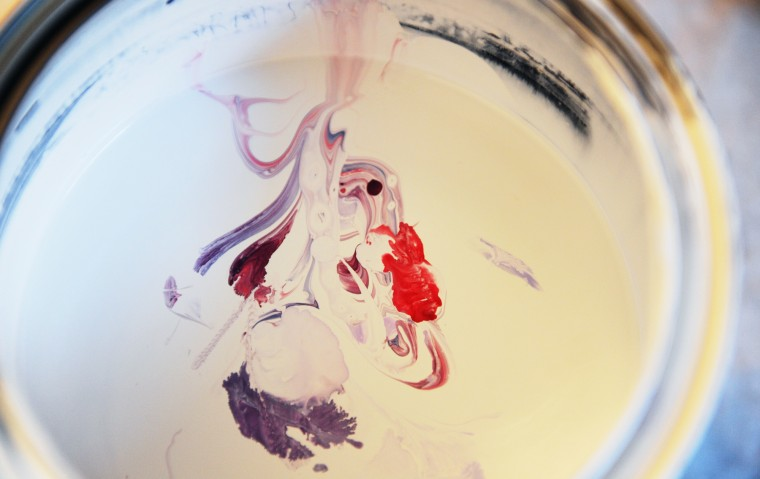 Reds and purple paints float on the surface of a white paint can at Edward Williams' Catonsville home studio, Tuesday, Jan. 14, 2014. (Jon Sham/BSMG)