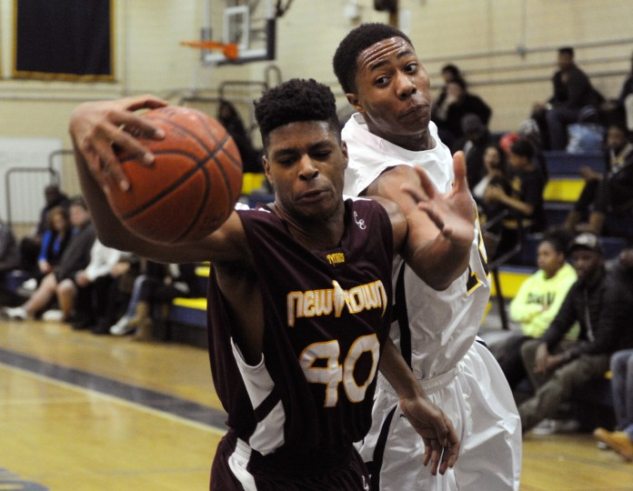 New Town's Juwan Dorsey, left, saves the ball from going out of bounds while Catonsville's Adam Ogbonuba tries to get a hand on it during a basketball game against at Catonsville High School on Wednesday, Jan. 8, 2013. (Jon Sham/BSMG)