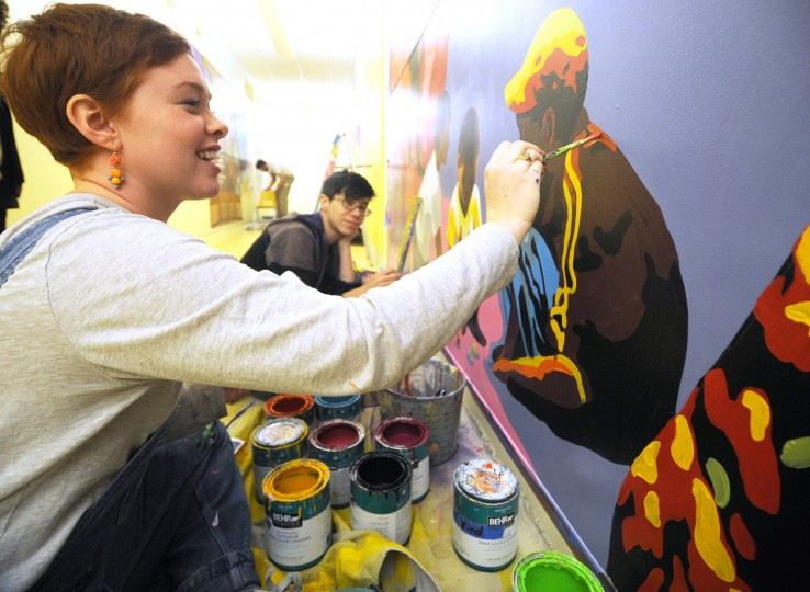 Hanna Moran, in the foreground, of Hampden, works on a mural at the Monarch Academy in Baltimore city with Laura Judkis, of Station North, on Wednesday, Nov. 13, 2013. (Jon Sham/BSMG)