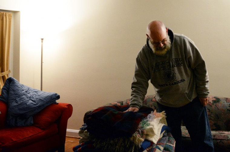 Rob Williams, a Rodgers Forge resident and Citizens on Patrol volunteer, stacks blankets in the living room of his home just after midnight on Thursday, Jan. 9, 2014 before taking them out to give to Towson's homeless to help during the recent cold snap. (Jon Sham/BSMG)
