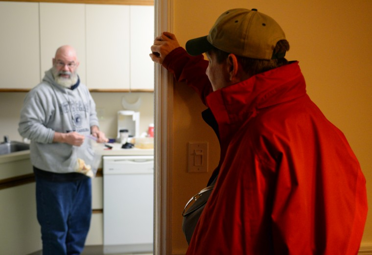 John Falconer, right, a fellow volunteer of Rob Williams, talks to his friend in the kitchen while he packs bread and soup to give to homeless people in Towson, Thursday, Jan. 9, 2014. (Jon Sham/BSMG)