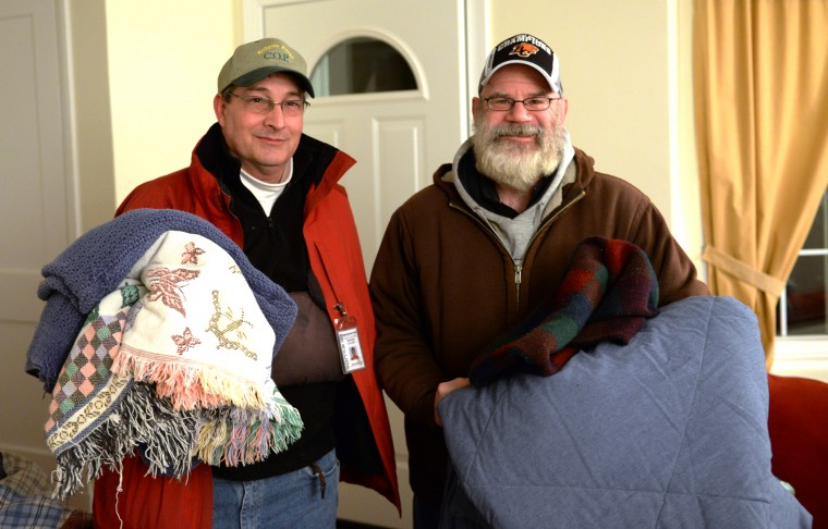 John Falconer, left, and Rob Williams pose for a photo in Williams' Rodgers Forge home holding on to some of the remaining blankets from their early morning trip around Towson to provide food and warmth to area homeless people. Thursday, Jan. 9, 2014. (Jon Sham/BSMG)
