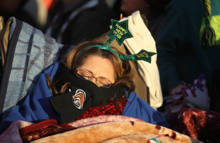 An early-arriving spectator takes a nap before the start of the 125th Rose Parade. (Rick Loomis/Los Angeles Times)