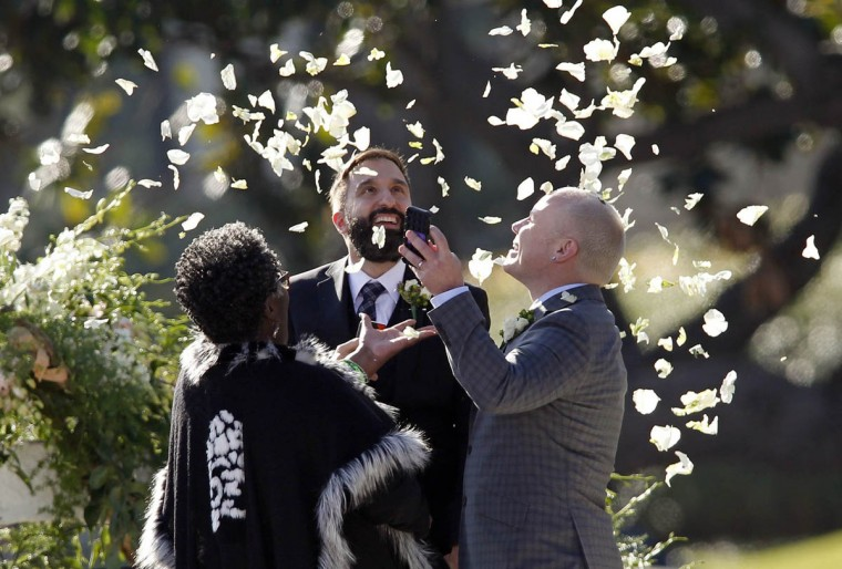 Danny Leclair, center, and Aubrey Loots, right, throw flower petals into the air after being married during the 125th Rose Parade in Pasadena, Calif., on Jan. 1, 2014. (Allen J. Schaben/Los Angeles Times)