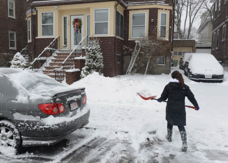 A woman shovels snow on Bayswater Street in East Boston, Massachusetts. An overnight blizzard is due to hit along the Northeast U.S. with six to twelve inches of accumulation expected in the Boston area along with coastal flooding. (Darren McCollester/Getty Images)