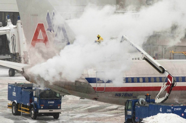 An American Airlines crew member sprays de-icing solution on a plane during a winter nor'easter snow storm in Boston, Massachusetts. Officials with Boston's Logan International Airport said they expected airlines to scale back operations during the storm, with the last departure expected at roughly 8:30 p.m. ET. (Dominick Reuter/Reuters photo)