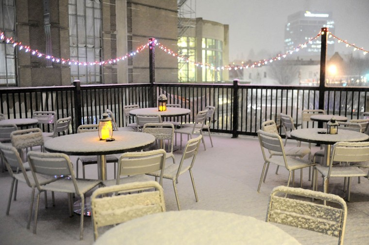 Snow accumulates on furniture on the new rooftop deck at The Greene Turtle in Towson during a celebration marking the deck's opening. (Steve Ruark/Patuxent)