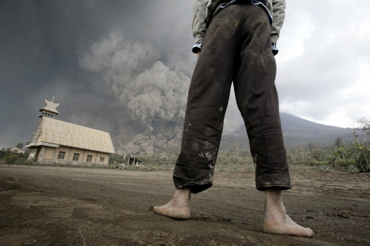 A resident looks on at giant volcanic ash clouds from a village in Karo district during the eruption of Mount Sinabung volcano located in Indonesia's Sumatra island on February 1, 2014. Chaideer Mahyuddin/AFP/Getty Images)