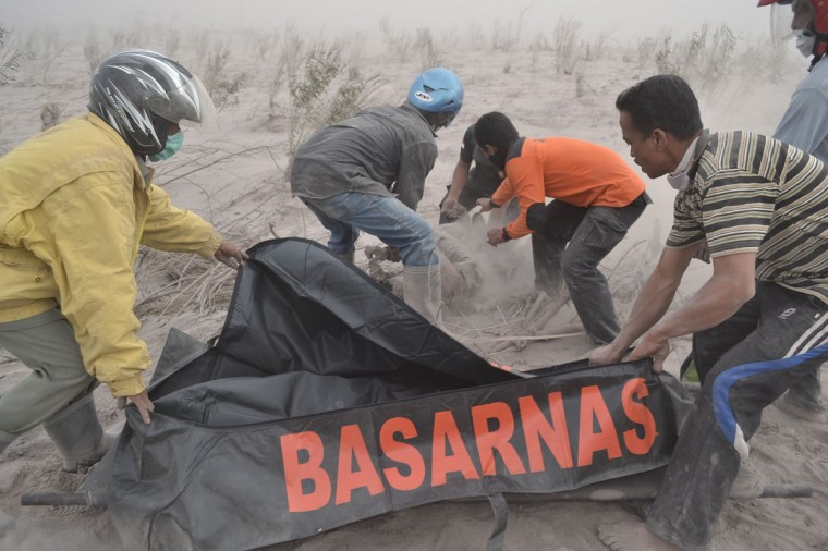 Rescuers recover the body of a victim at a village in Karo district following eruptions of Mount Sinabung located in Indonesia's Sumatra island on February 1, 2014. (Sutanta Adiya/AFP/Getty Images)